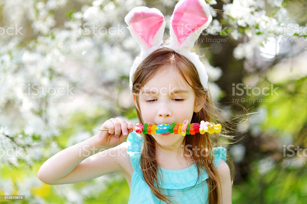 Adorable little girl eating colorful gum candies on Easter stock photo