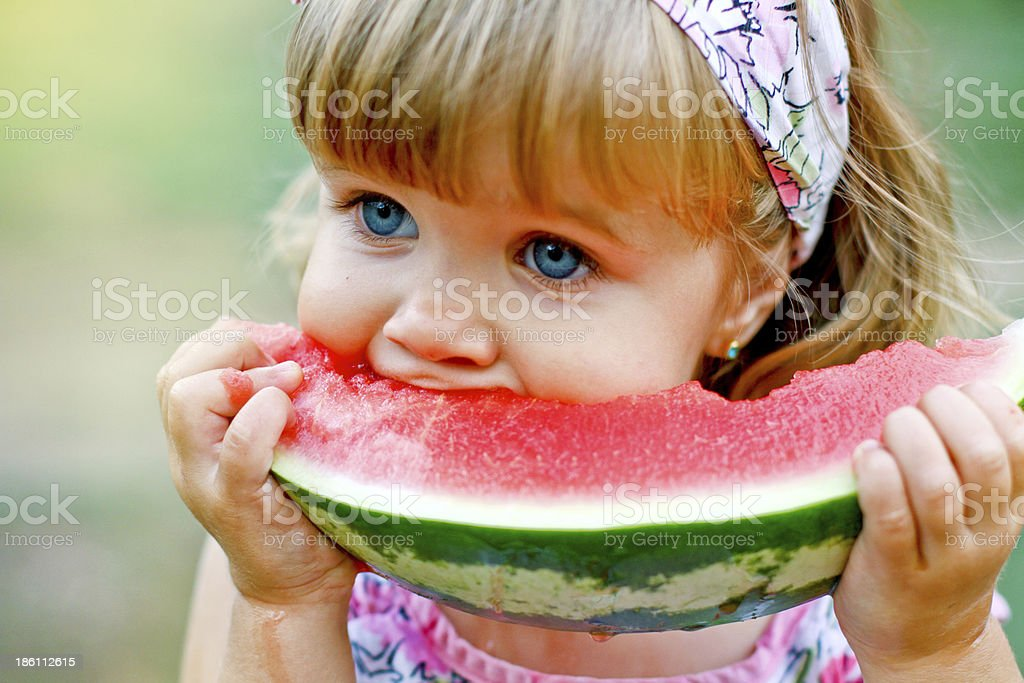 Adorable little girl eats a slice of watermelon outdoors stock photo