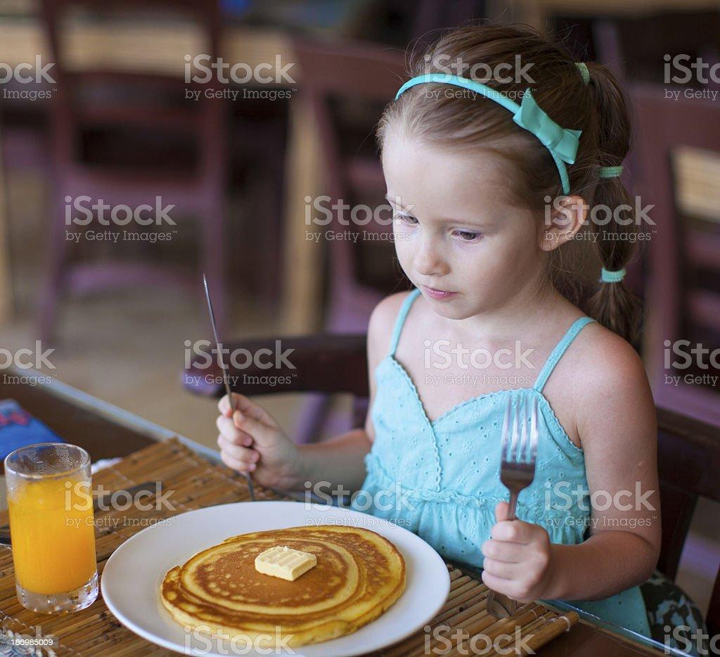 Adorable little girl having breakfast at resort restaurant royalty-free stock photo