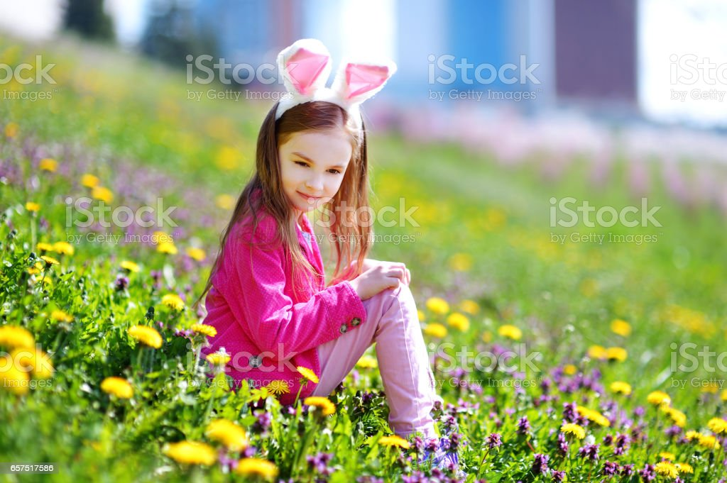 Adorable little girl in blooming meadow stock photo