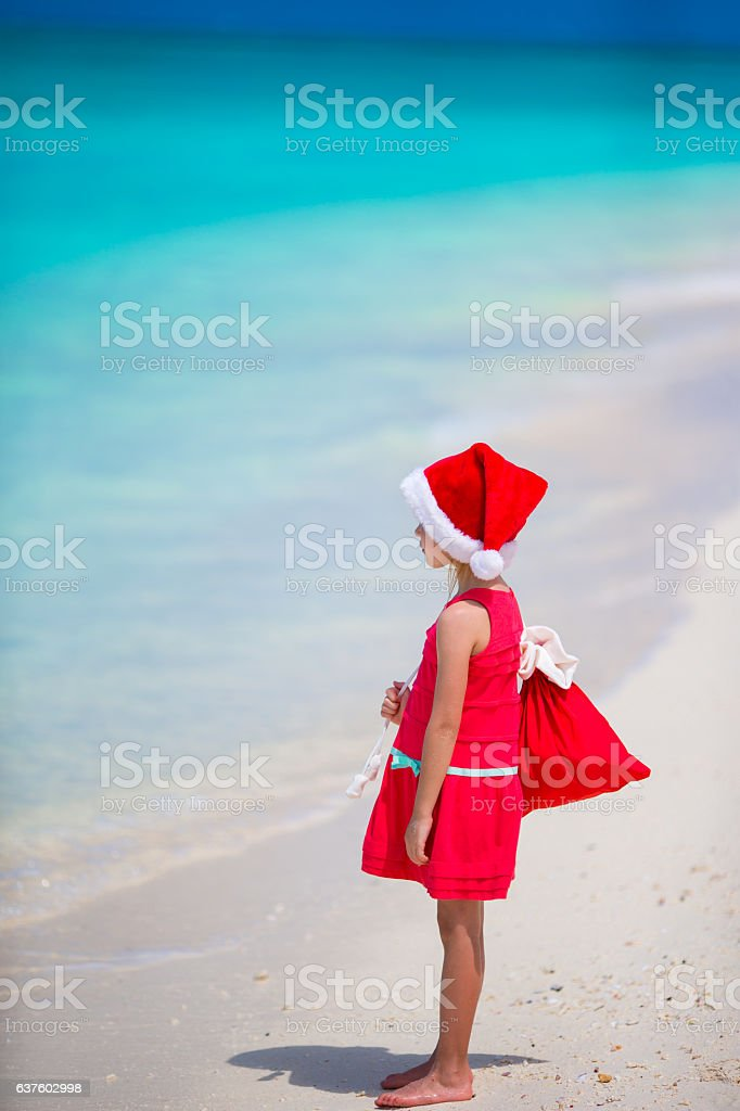 Adorable little girl in Santa hat during Christmas beach vacation stock photo