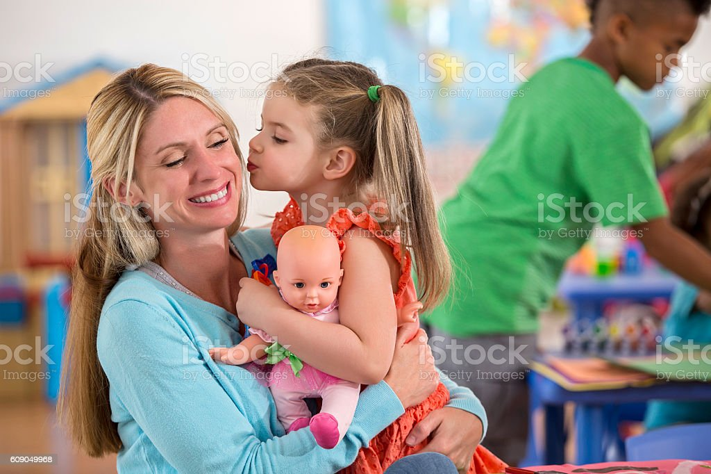 Adorable little girl kisses her mother goodbye at daycare center stock photo