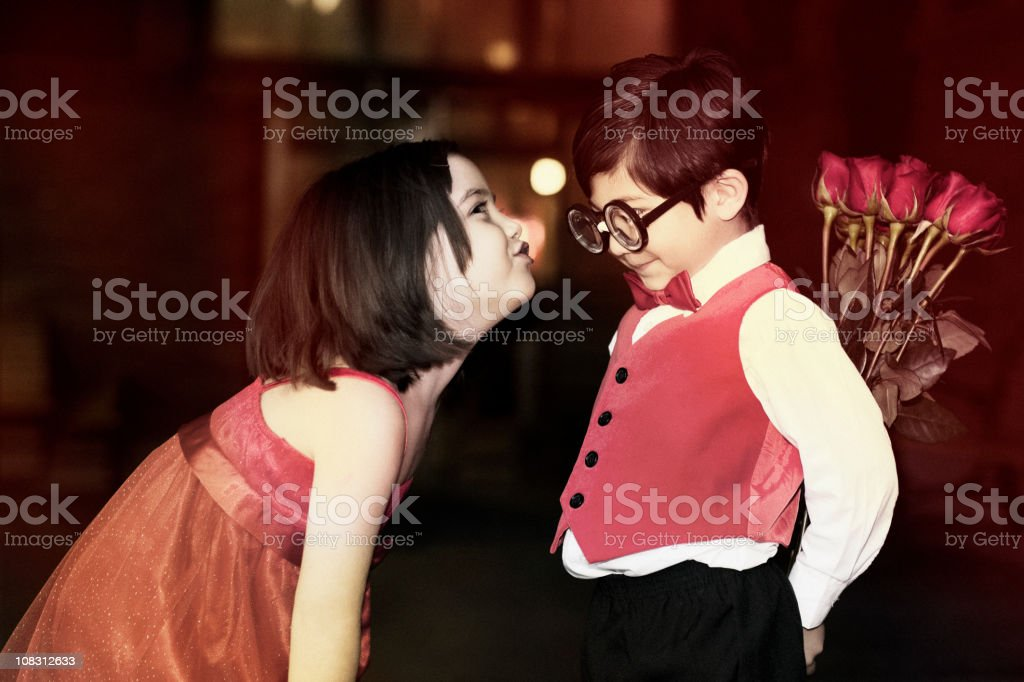 Adorable Little Girl Kissing Shy Boy with Bouquet of Roses royalty-free stock photo