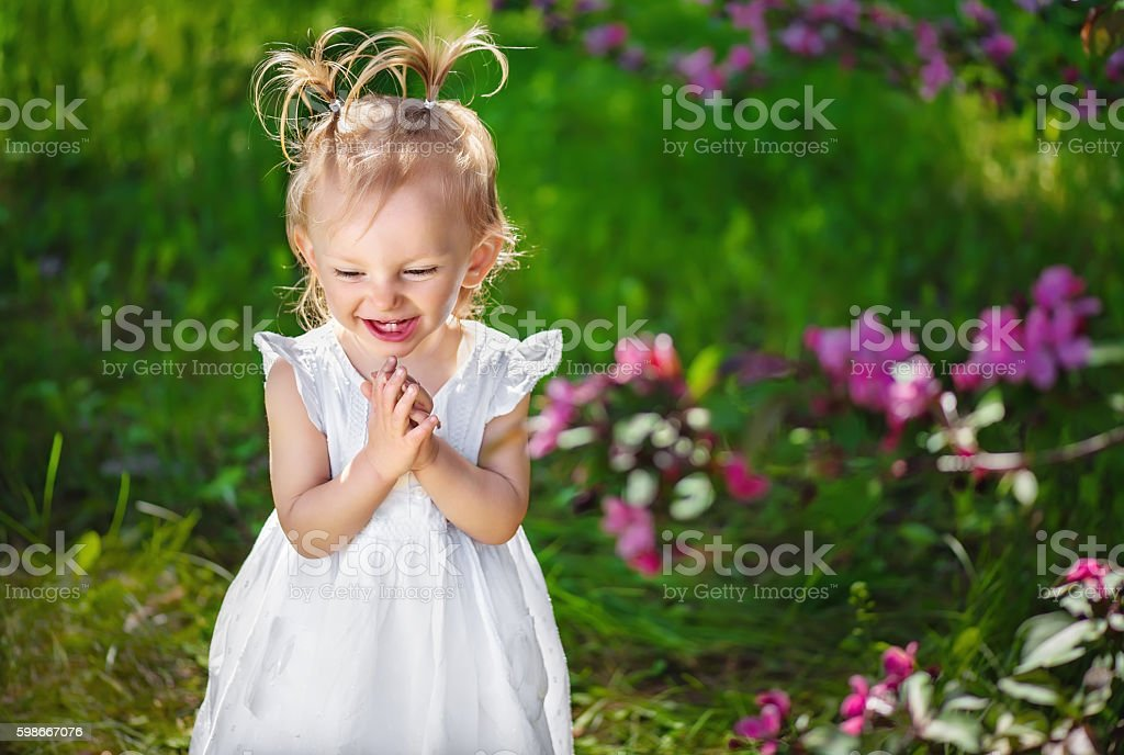 adorable little girl laughing and playing their hands stock photo