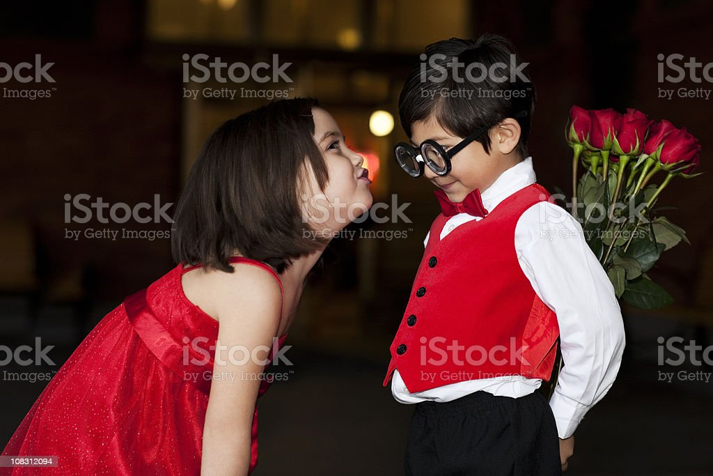Adorable Little Girl Leans in to Kiss Nerdy Shy Boy royalty-free stock photo