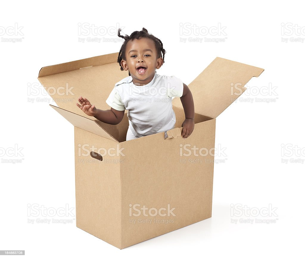 Adorable little girl leaping up out of a box royalty-free stock photo