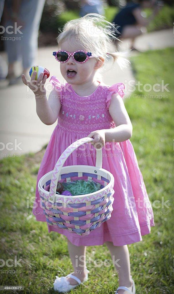 Adorable little girl on Easter egg hunt stock photo