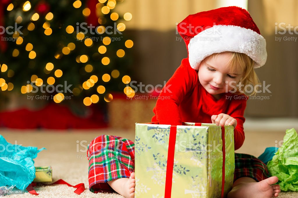 Adorable little girl opening christmas gift stock photo