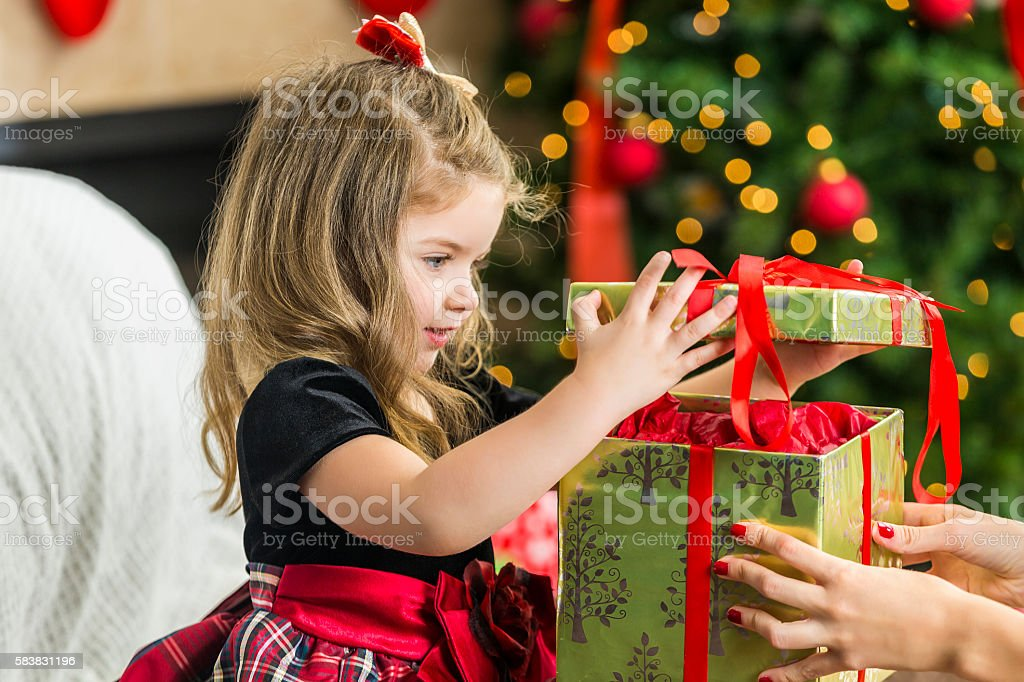 Adorable little girl opening her Christmas present stock photo
