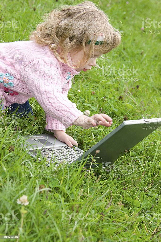 Adorable little girl playing with laptop royalty-free stock photo