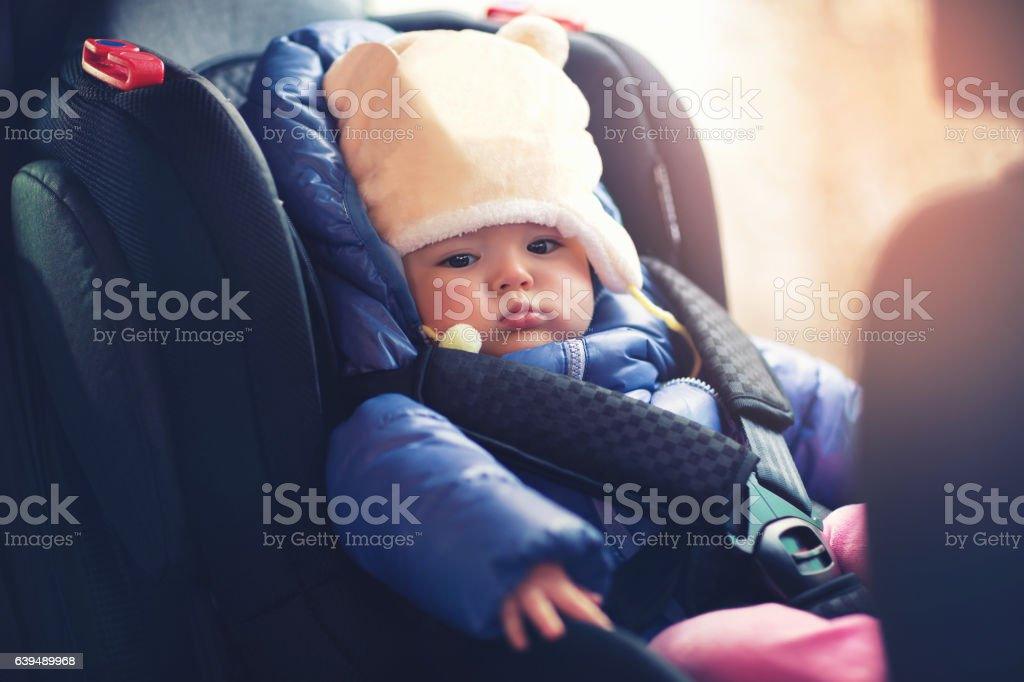 Adorable little girl sitting in car in winter clothes stock photo