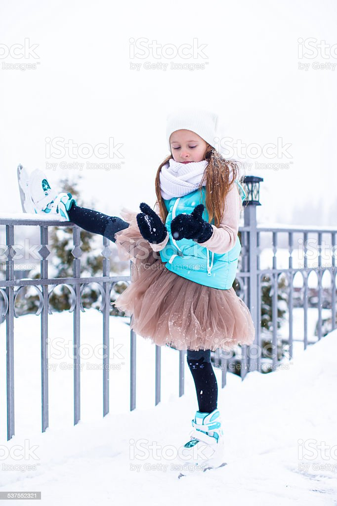 Adorable little girl skating in winter snow day stock photo