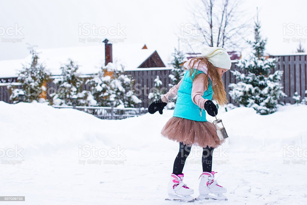 Adorable little girl skating in winter snowy day outdoors stock photo