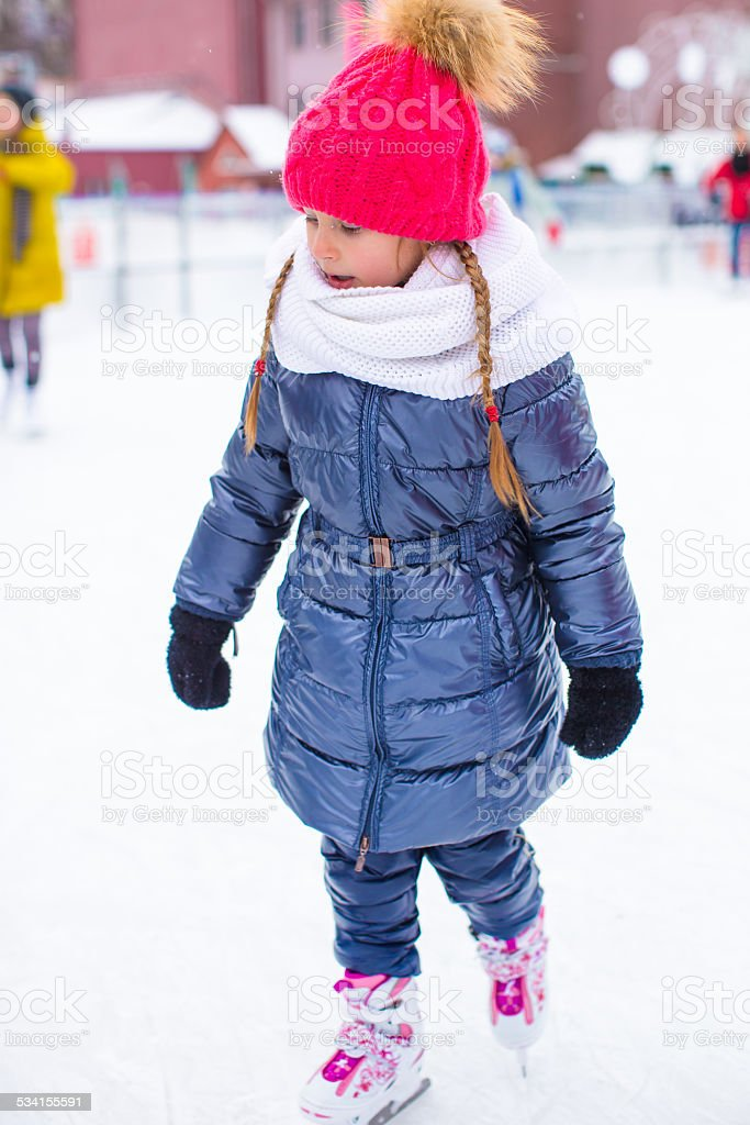 Adorable little girl skating on the ice rink outdoors stock photo