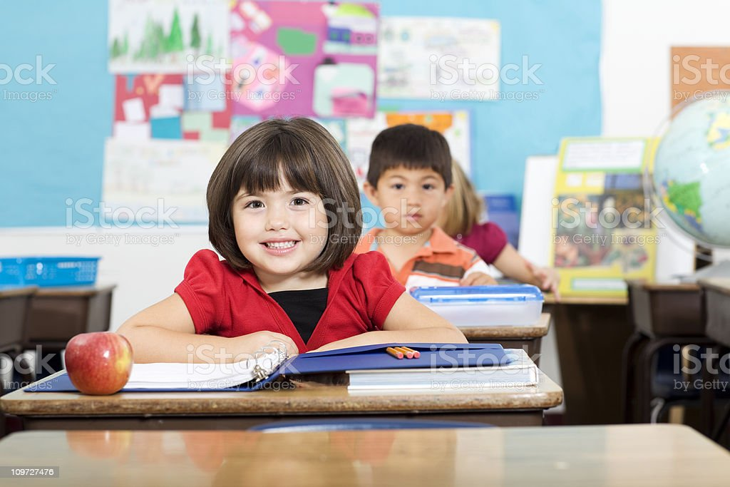 Adorable Little Girl Smiling in Elementary Classroom, Copy Space royalty-free stock photo