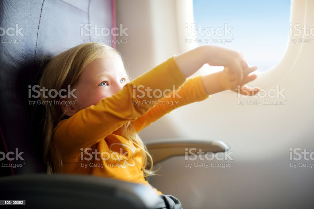 Adorable little girl traveling by an airplane. Child sitting by aircraft window and looking outside. stock photo
