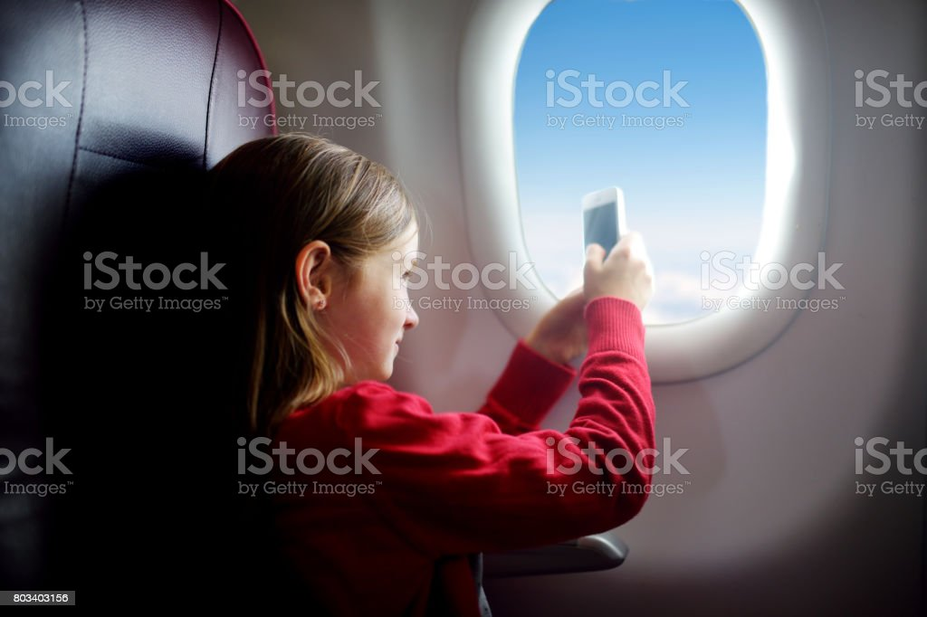 Adorable little girl traveling by an airplane. Child sitting by aircraft window taking pictures of the sky. stock photo