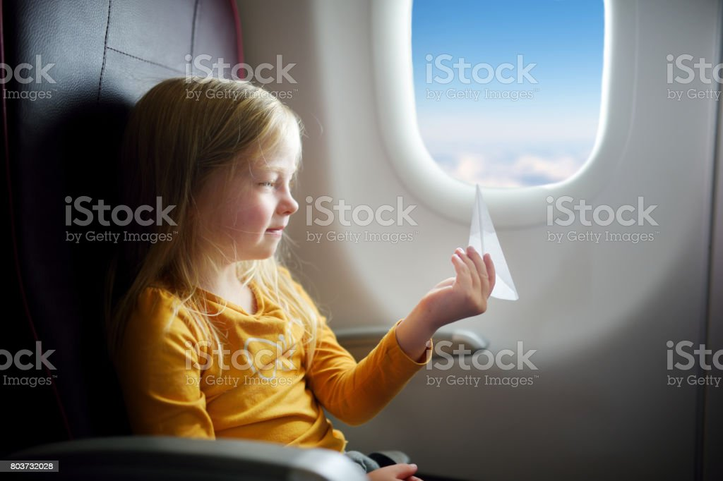 Adorable little girl traveling by an airplane. Child sitting by aircraft window playing with paper plane. stock photo