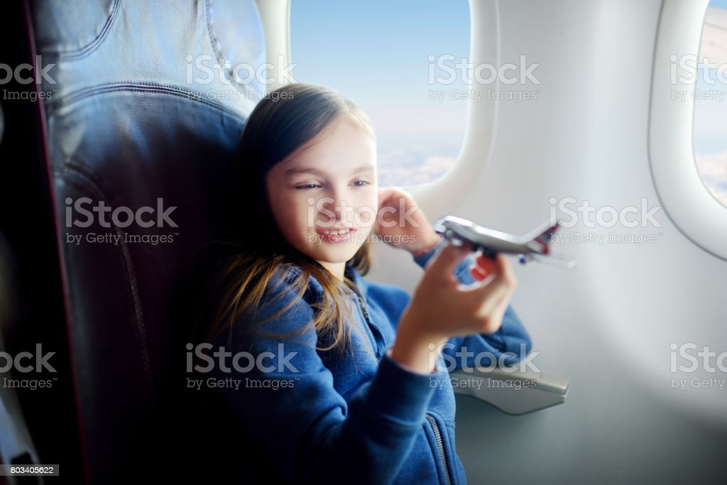 Adorable little girl traveling by an airplane. Child sitting by the window and playing with toy plane. stock photo