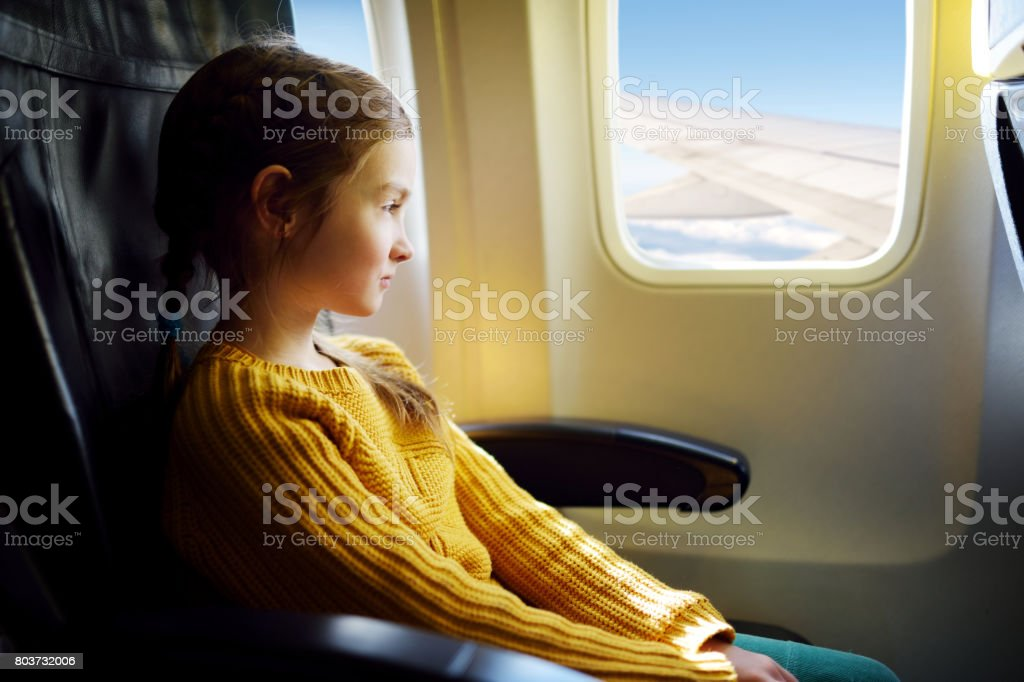 Adorable little girl traveling by an airplane stock photo
