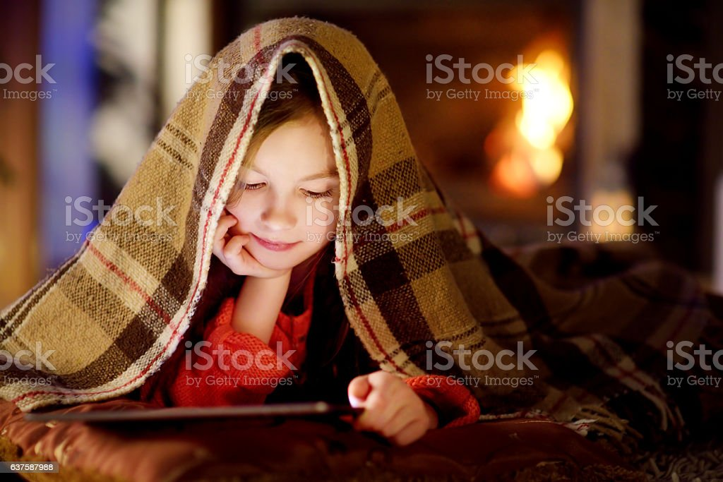 Adorable little girl using tablet by fireplace on Christmas evening stock photo