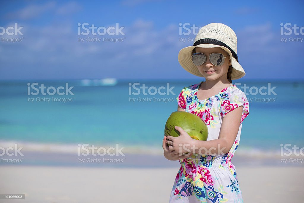 Adorable little girl with coconut at white beach stock photo