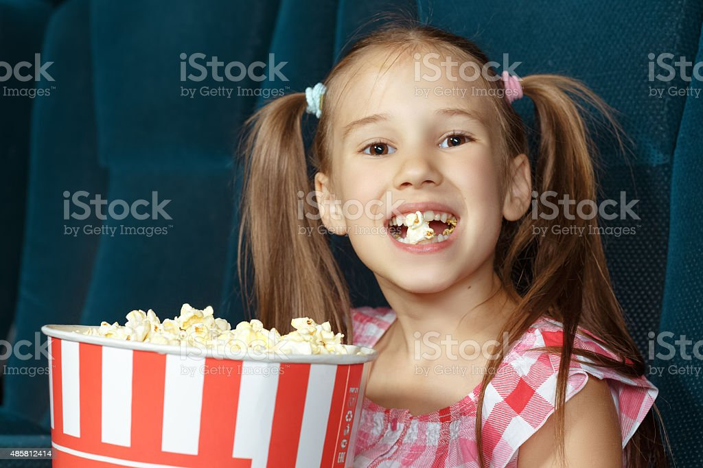 Adorable little girl with popcorn stock photo