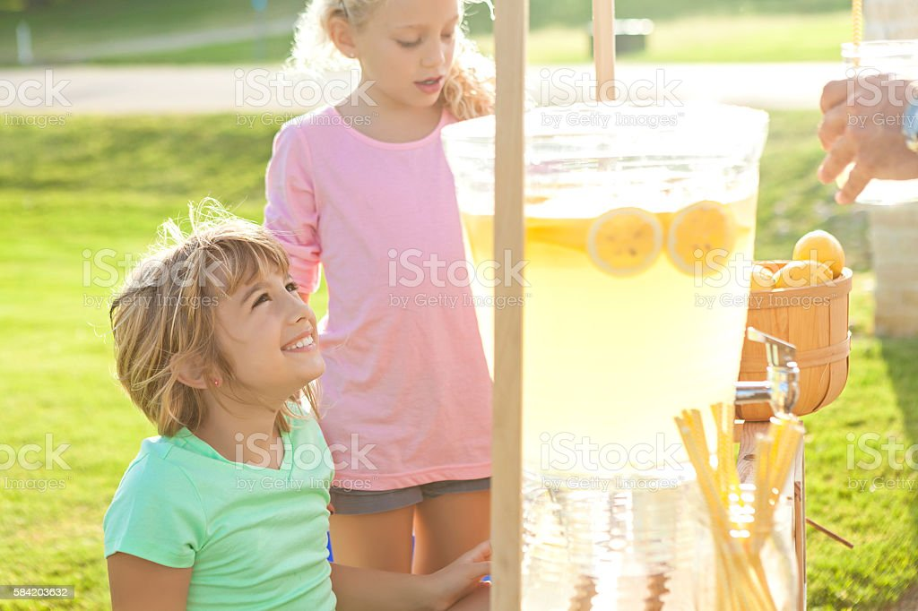 Adorable little girls selling lemonade on a hot summer day stock photo