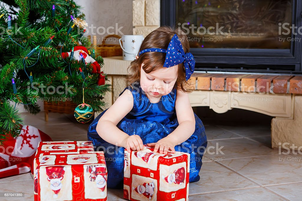 Adorable little kid girl celebrating Christmas holiday at home stock photo