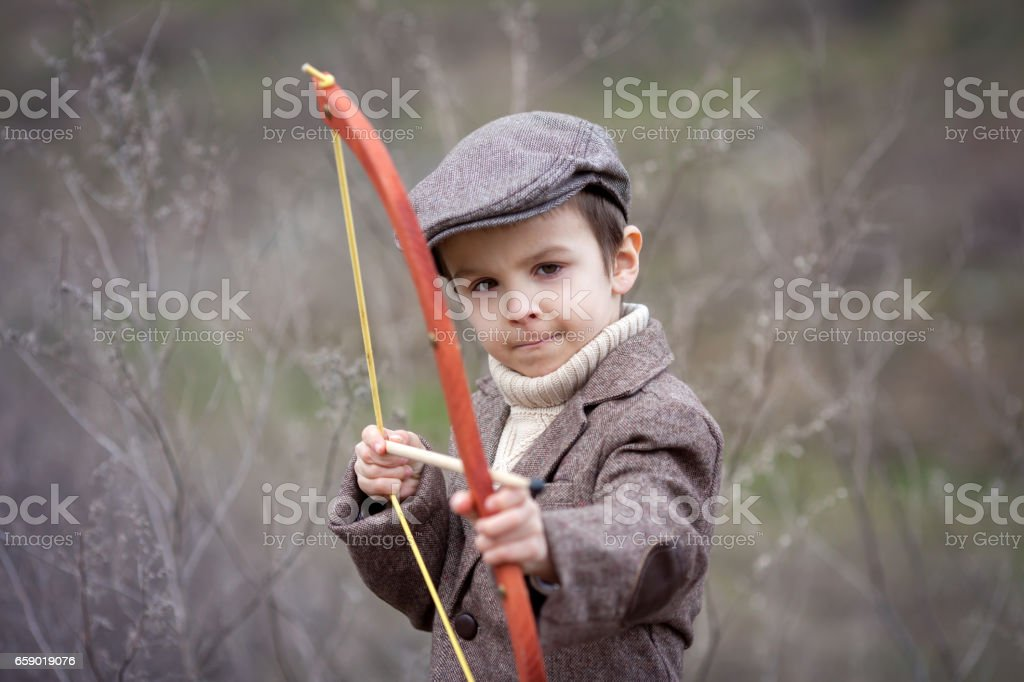 Adorable little preschool boy, shoot with bow and arrow at target in open air, springtime outdoors stock photo