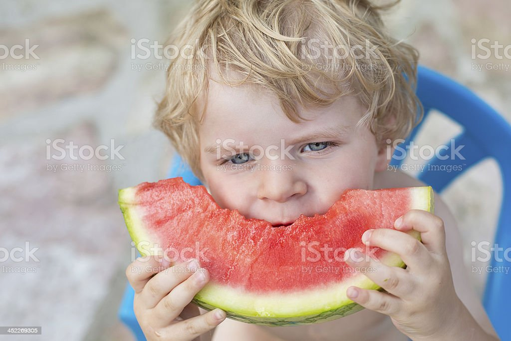 Adorable little toddler boy with blond hairs eating watermelon i royalty-free stock photo
