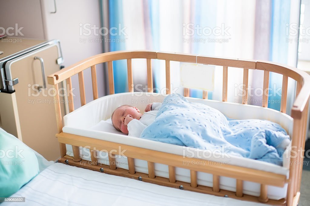 Adorable newborn baby boy in hospital cot stock photo