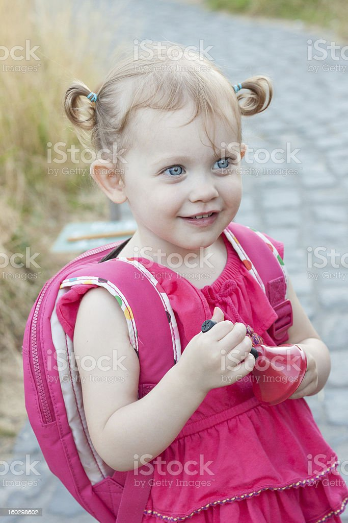 Adorable Preschool Girl with Pigtails and BackPack holding School Bell royalty-free stock photo