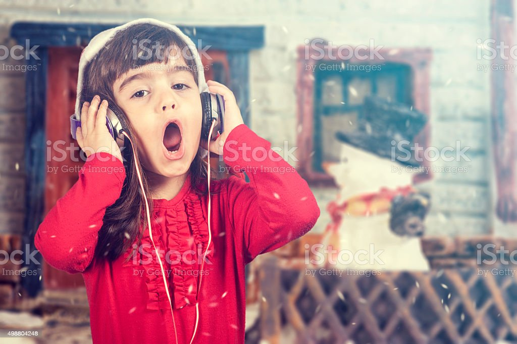 Adorable Santa girl listening to music and singing Christmas carols stock photo