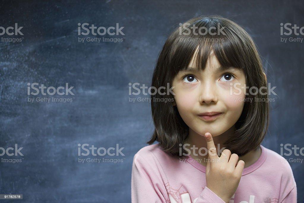 Adorable schoolgirl stay near school blackboard. royalty-free stock photo