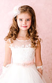 Adorable smiling little girl in white princess dress