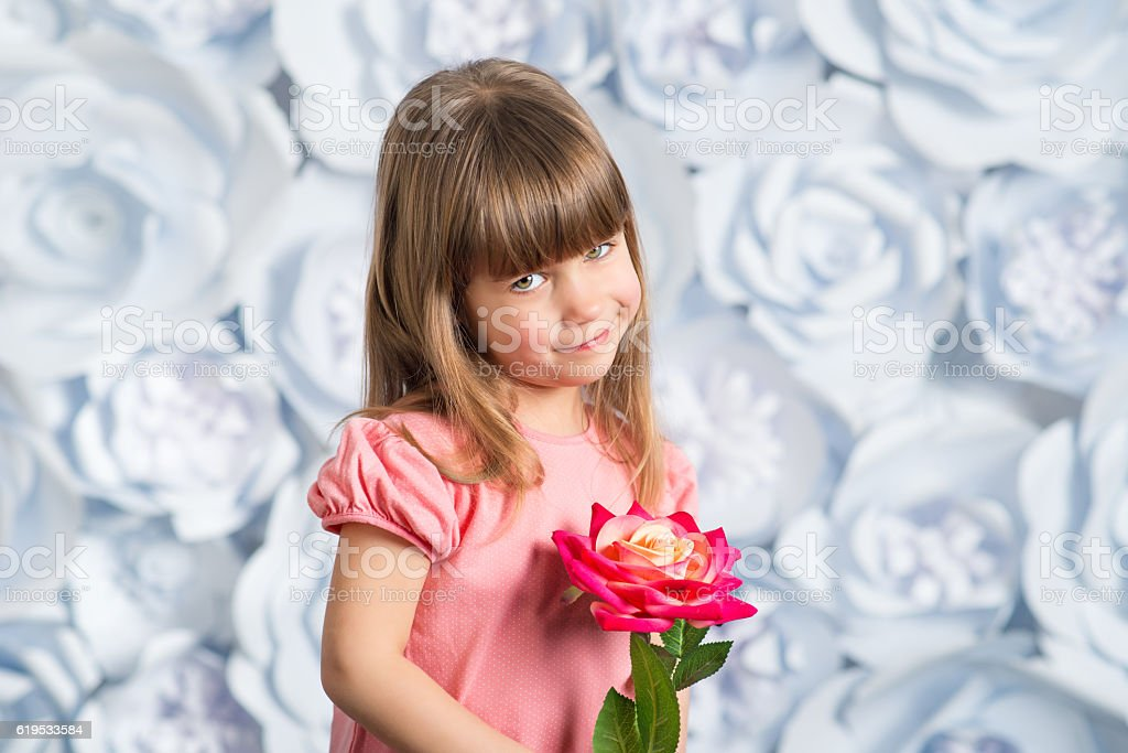 Adorable smiling little girl with artificial flower stock photo