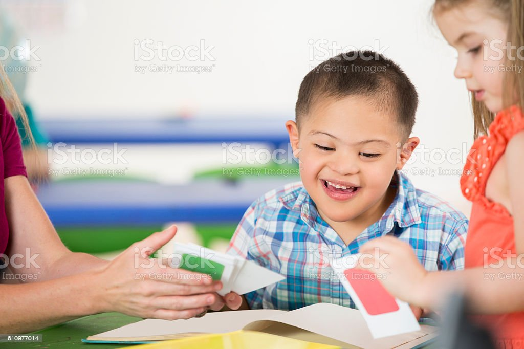 Adorable special needs boy works with therapist stock photo