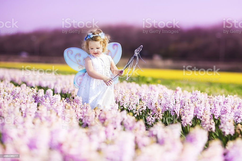 Adorable toddler girl in fairy costume playing on flower field stock photo