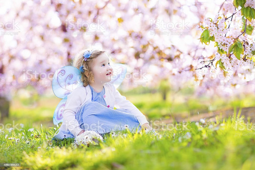 Adorable toddler girl in fairy costume under cherry blossom trees stock photo