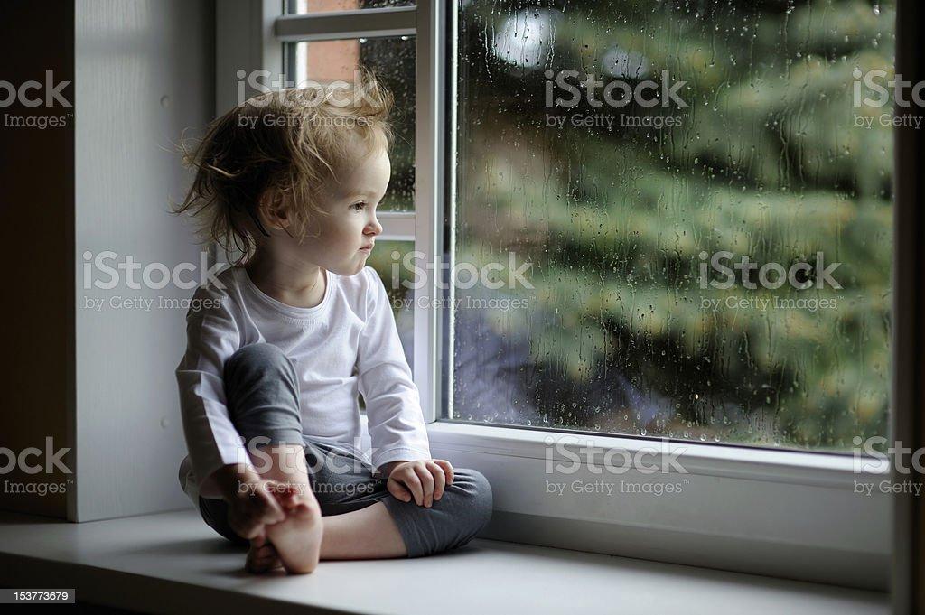 Adorable toddler girl looking at raindrops royalty-free stock photo