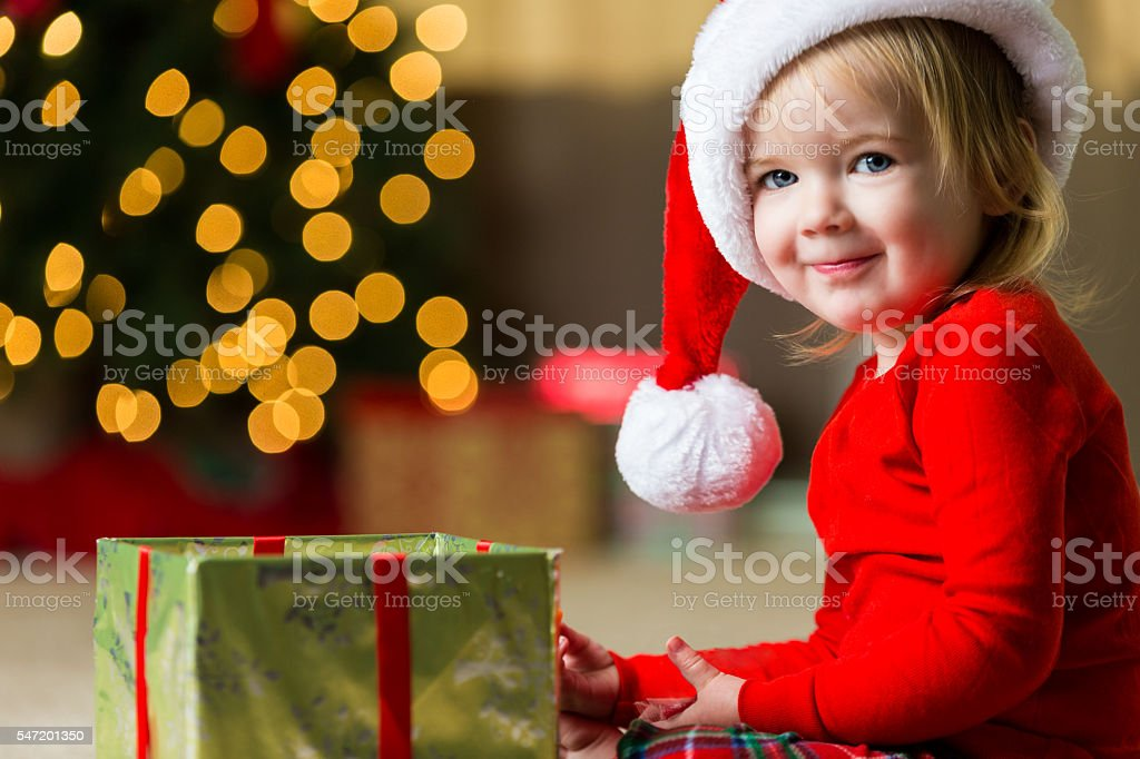 Adorable toddler girl opening Christmas gift stock photo