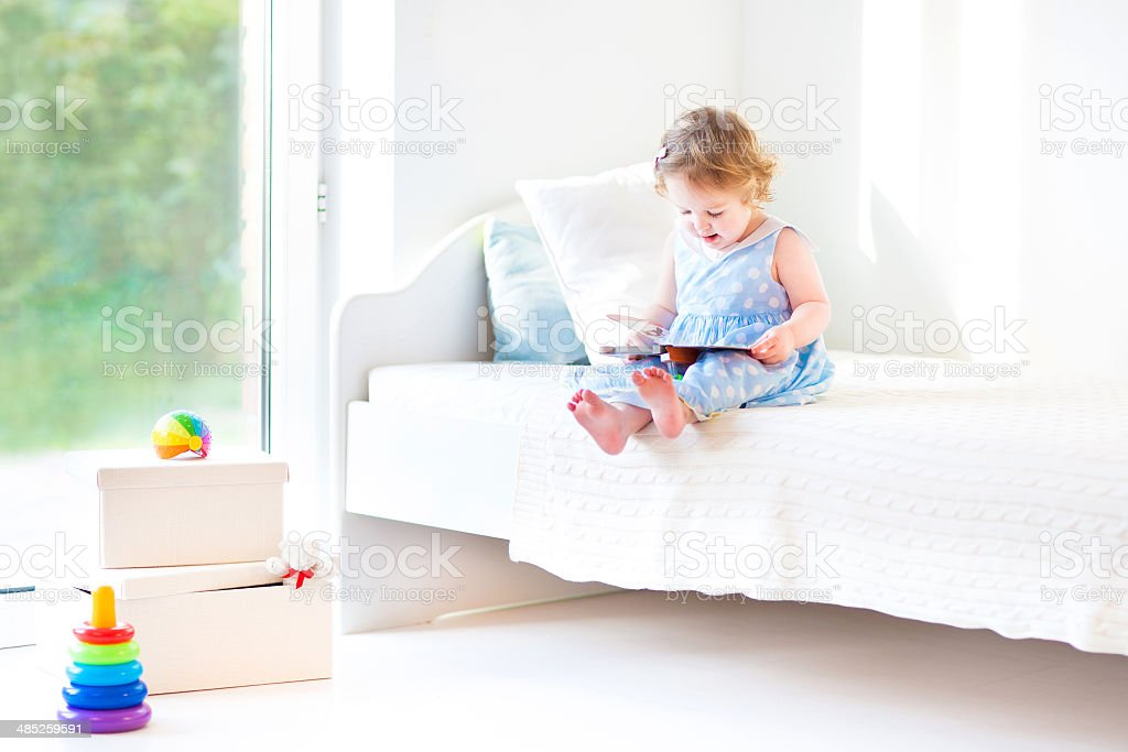 Adorable toddler girl reading book sitting on white bed stock photo