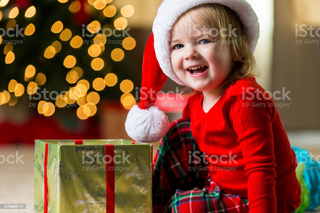Adorable toddler opens gift on Christmas morning stock photo