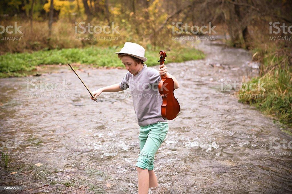 Adorable Young Boy Wading Through Creek with His Violin stock photo