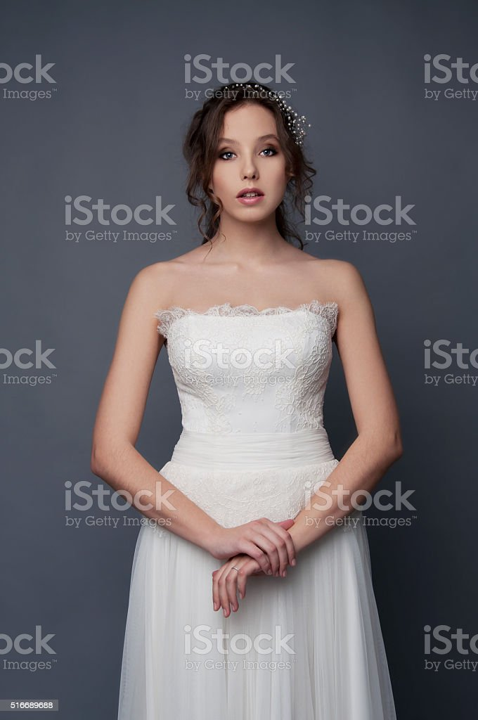 Adorable young bride with brown curly hair and pearl headpiece stock photo