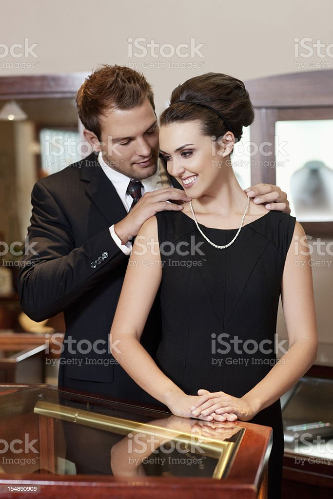 Adorable Young Couple with Necklace Gift in Jewelry Store stock photo