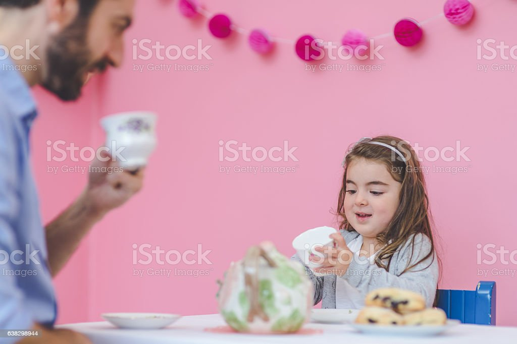 Adorable young girl having a tea party with her father stock photo