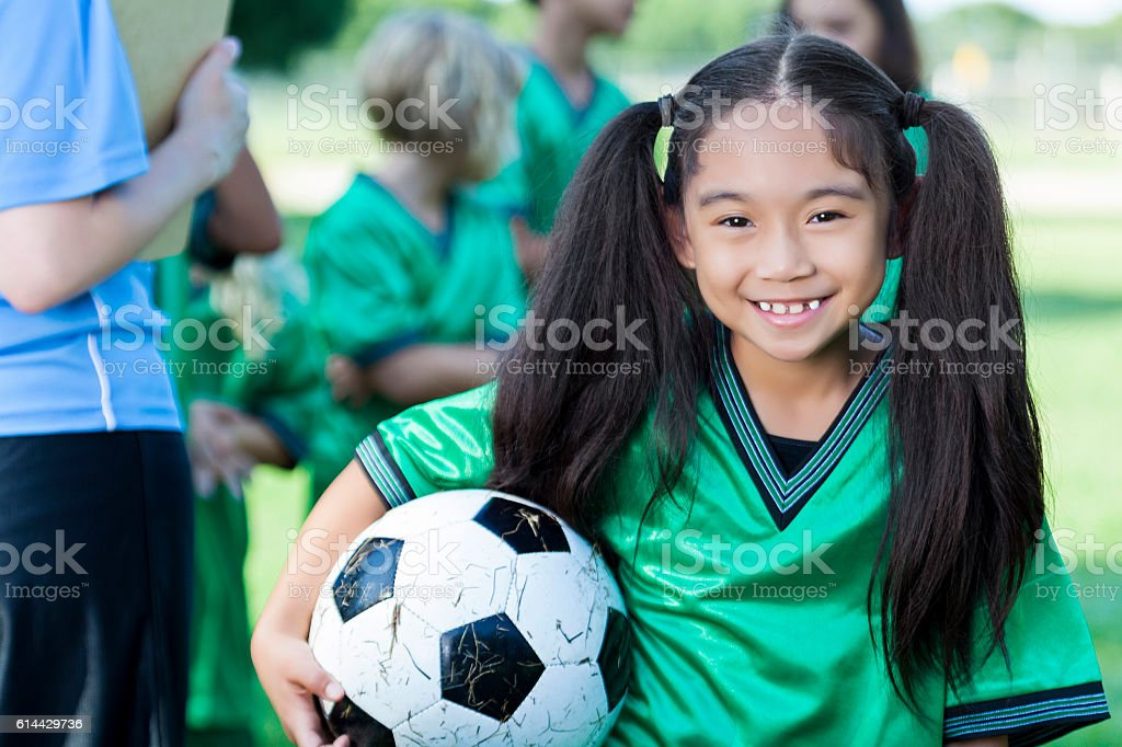 Adorable young girl holds soccer ball stock photo