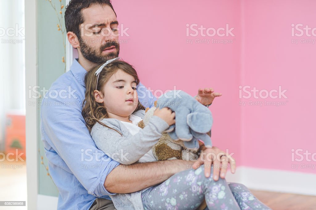 Adorable young girl sitting on the ground with her stock photo